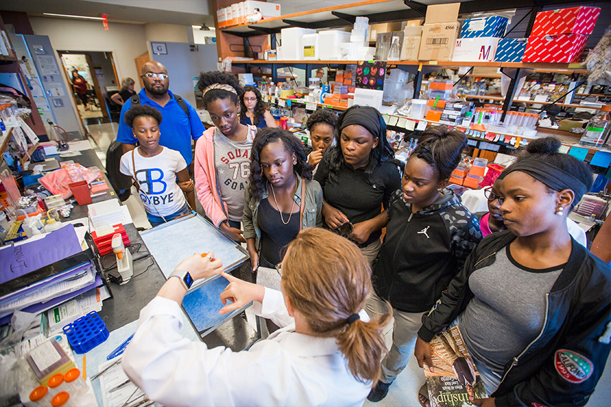 a group of high school students tour a lab